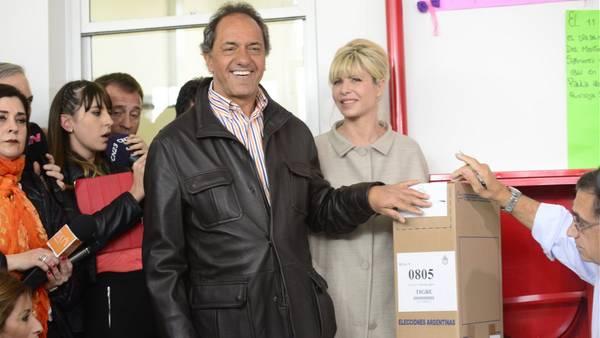 El candidato a la presidencia por el Frente para la Victoria Daniel Scioli emite su voto junto a su esposa.
