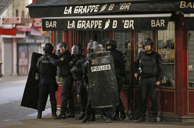 Police officers take up positions in Saint Denis, a northern suburb of Paris, Wednesday, Nov. 18, 2015. Authorities in the Paris suburb of Saint Denis are telling residents to stay inside during a large police operation near France's national stadium that two officials say is linked to last week's deadly attacks. (AP Photo/Francois Mori)