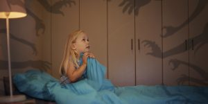 Shot of a frightened little girl being kept awake by scary shadows