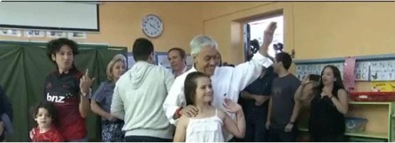 """Piñera vota y detrás un hombre le hace un """"hoyudo"""" que nadie percibió"""
